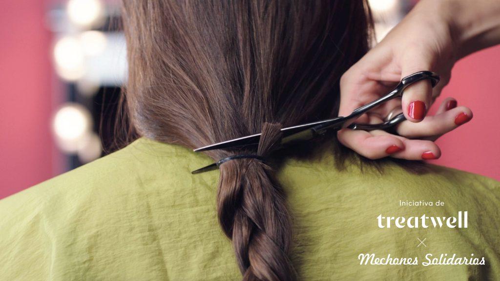 Imagen de la campaña de donación de pelo por la cadena de salones Tratwell. En la imagen se muestra unas tijeras costando una coleta.
